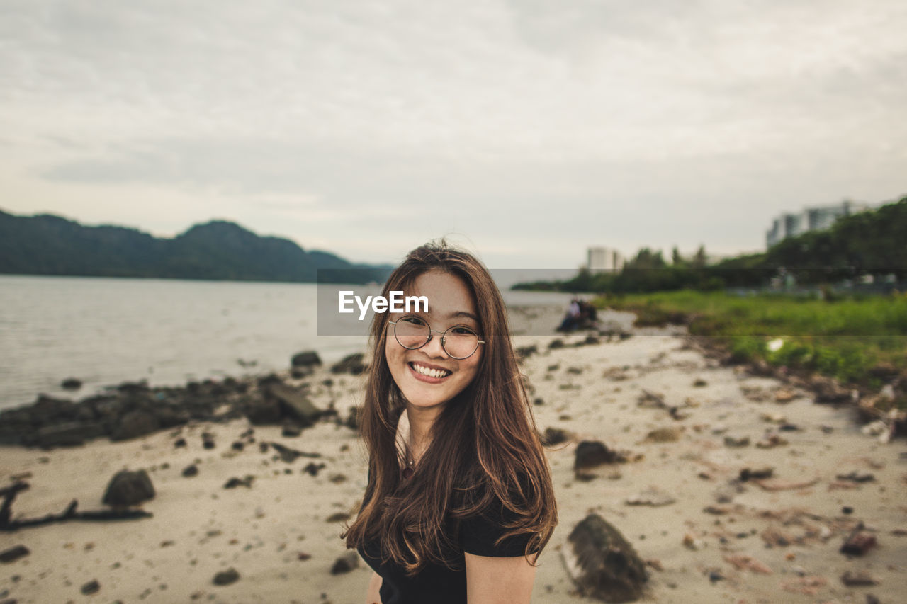 Side View Portrait Of Cheerful Woman Standing At Beach