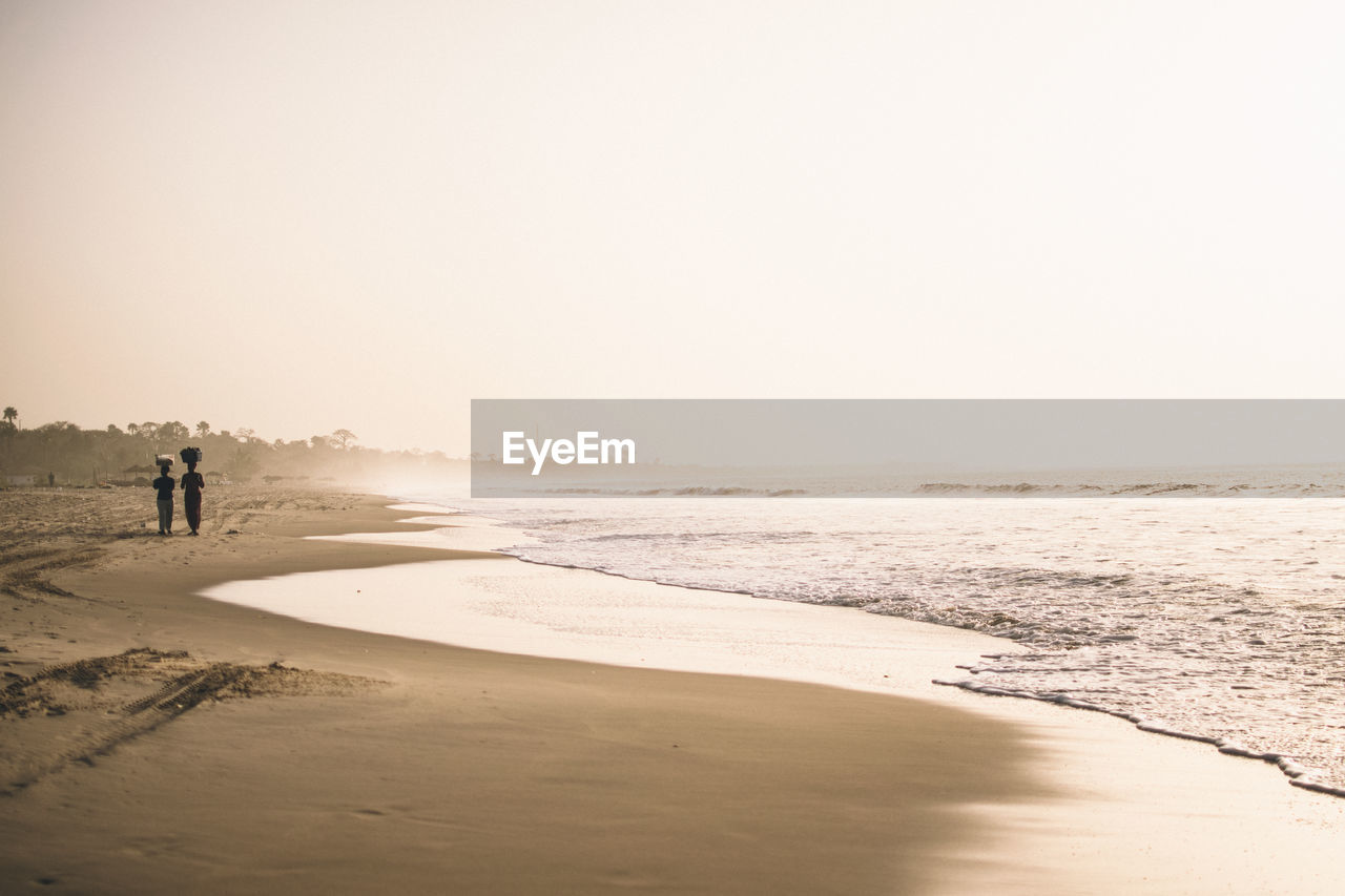land, beach, sea, sky, water, sand, scenics - nature, nature, beauty in nature, real people, copy space, tranquility, tranquil scene, leisure activity, lifestyles, clear sky, people, two people, day, outdoors, horizon over water