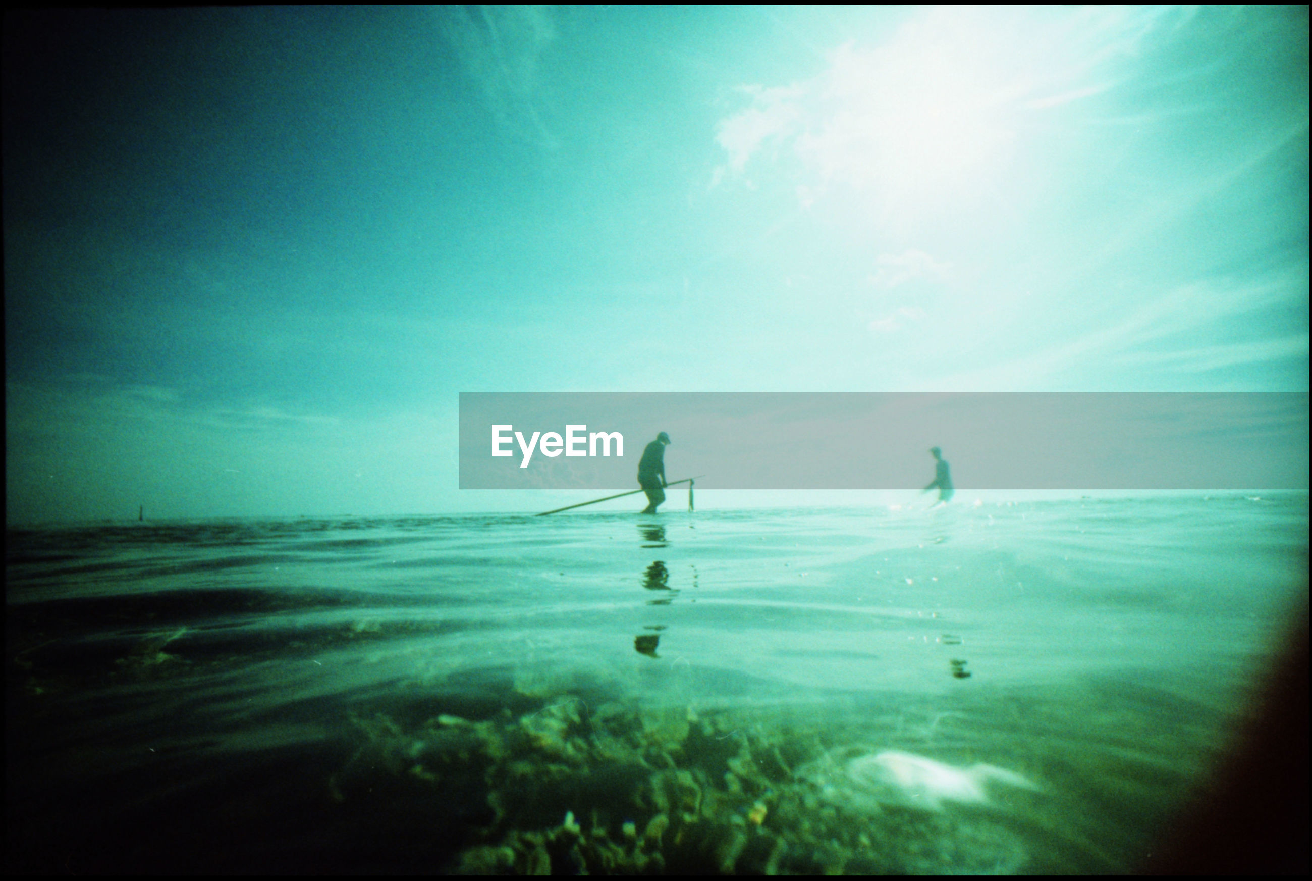 Silhouette man in calm blue sea