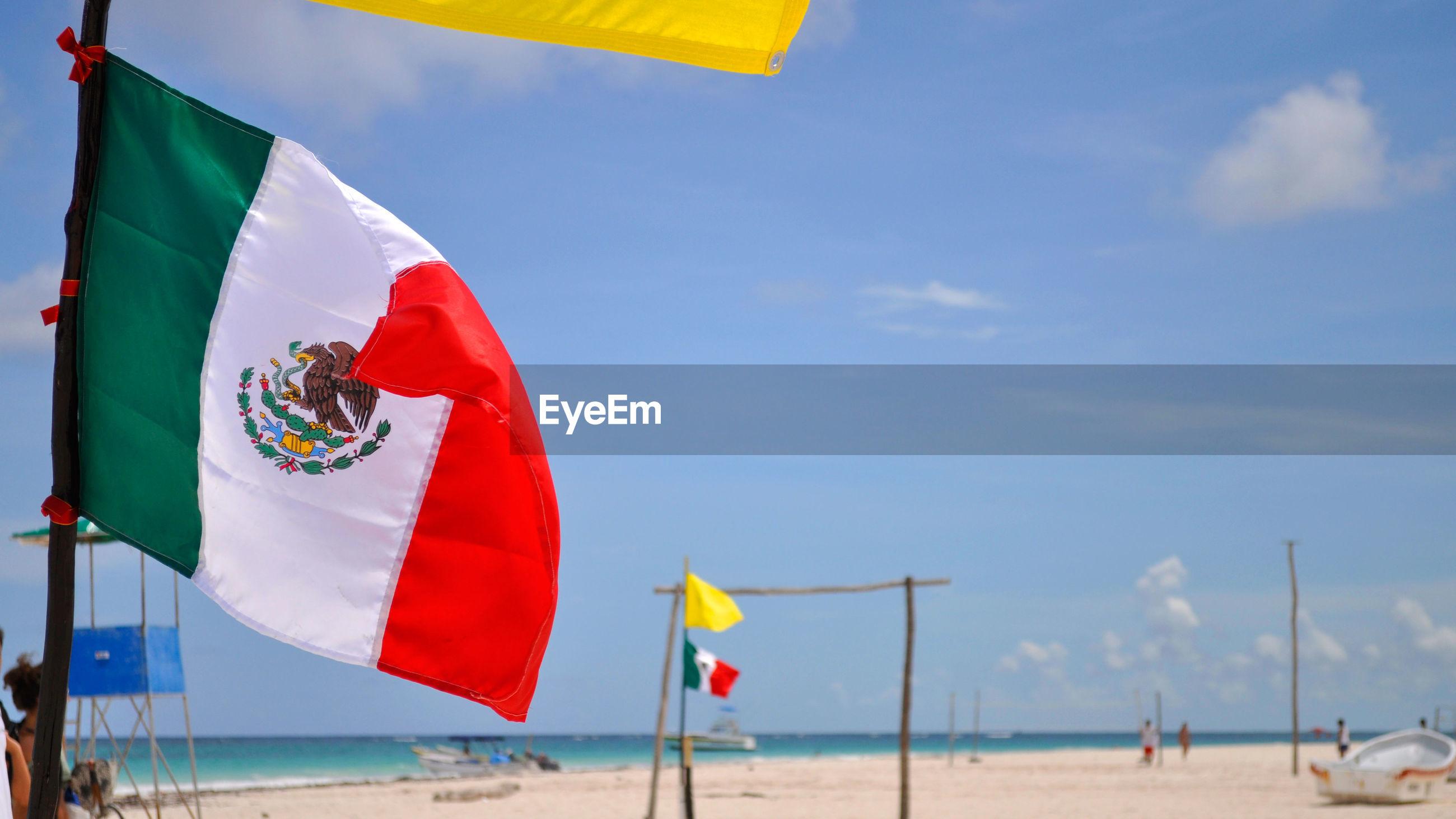 Mexican flag on beach against sky