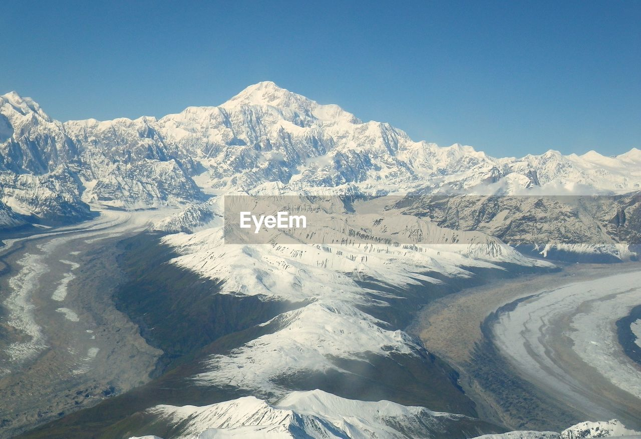 Majestic shot of snow capped mountains against clear sky
