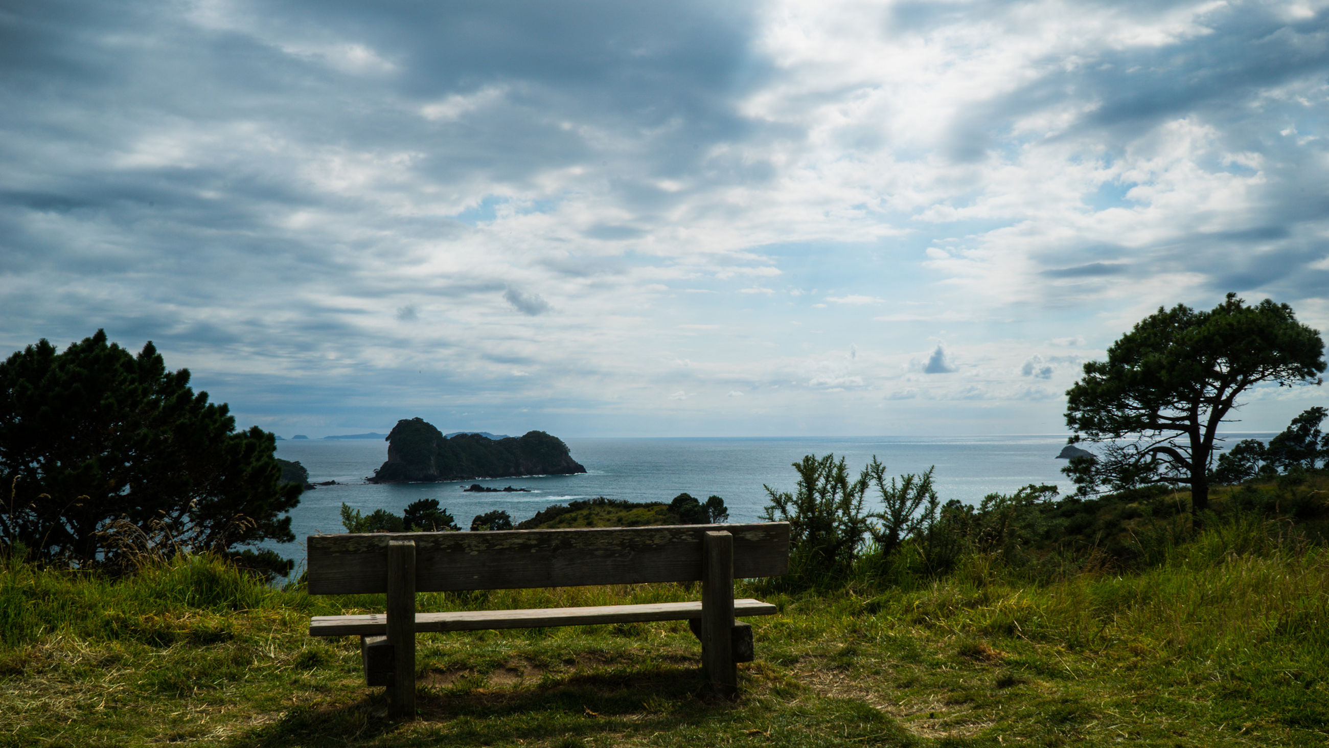 Empty bench by sea against sky