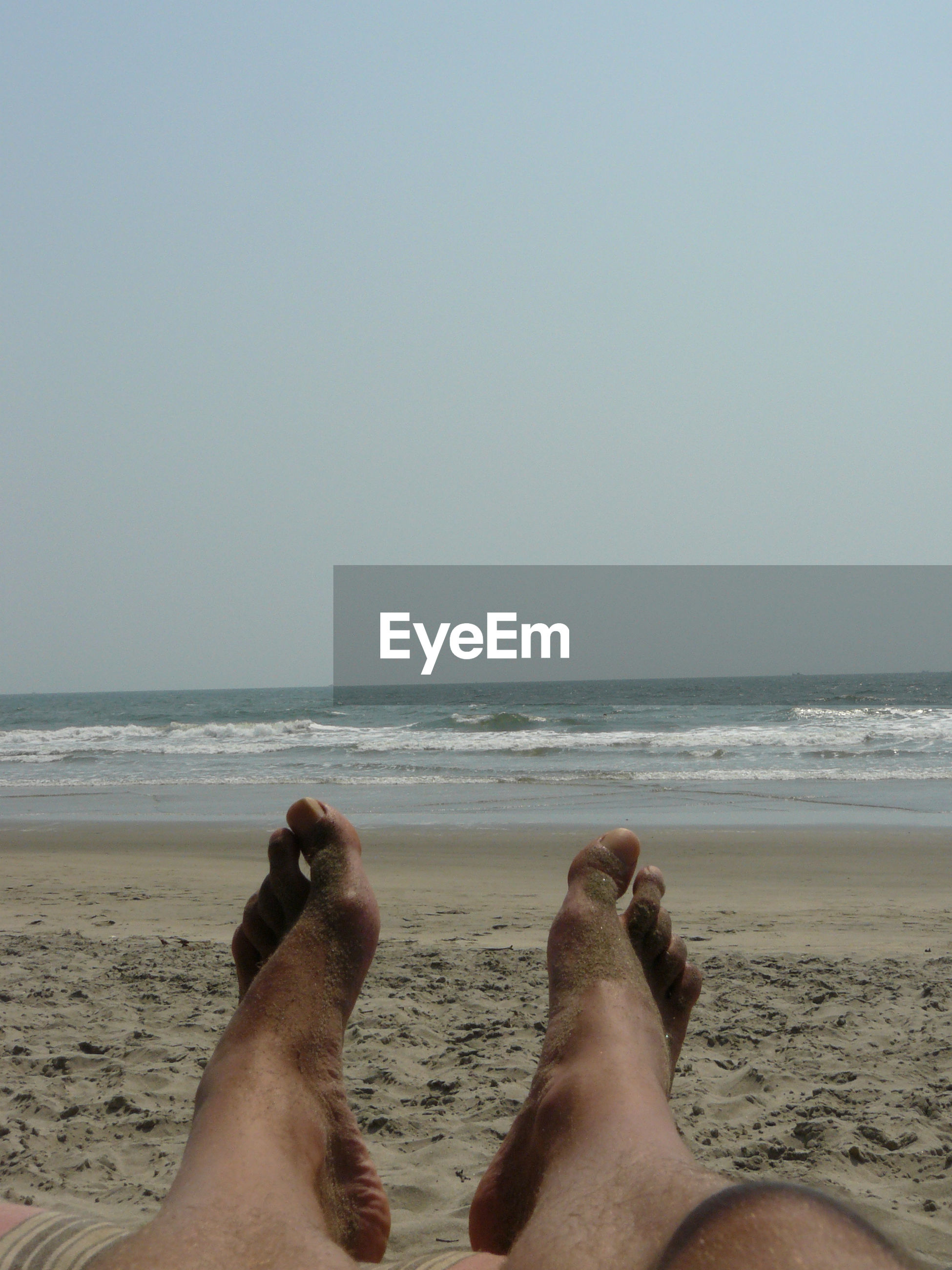 Low section of man legs at beach against clear sky