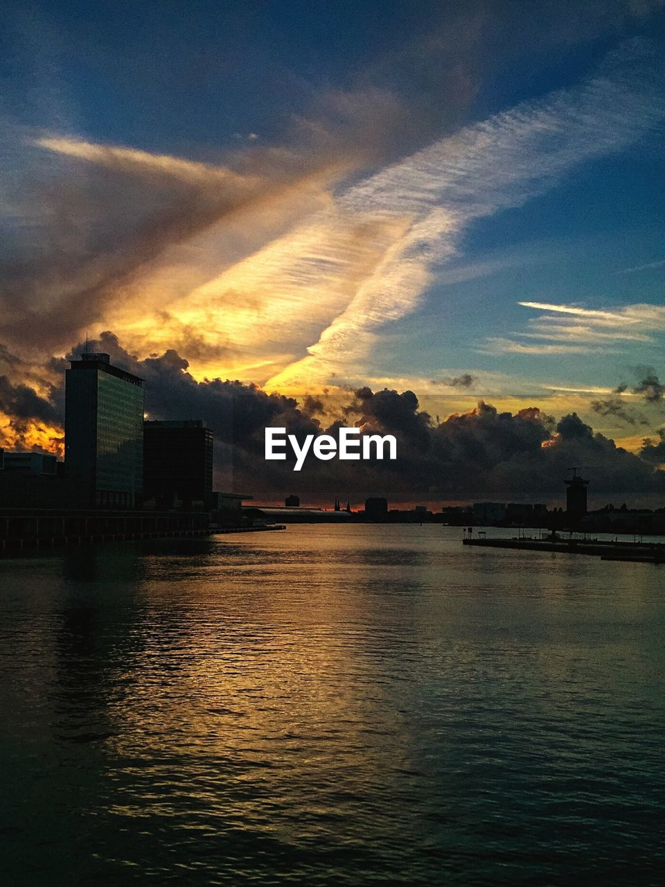 architecture, built structure, sky, building exterior, sunset, cloud - sky, no people, water, waterfront, reflection, silhouette, outdoors, river, city, skyscraper, nature, tranquility, beauty in nature, modern, day