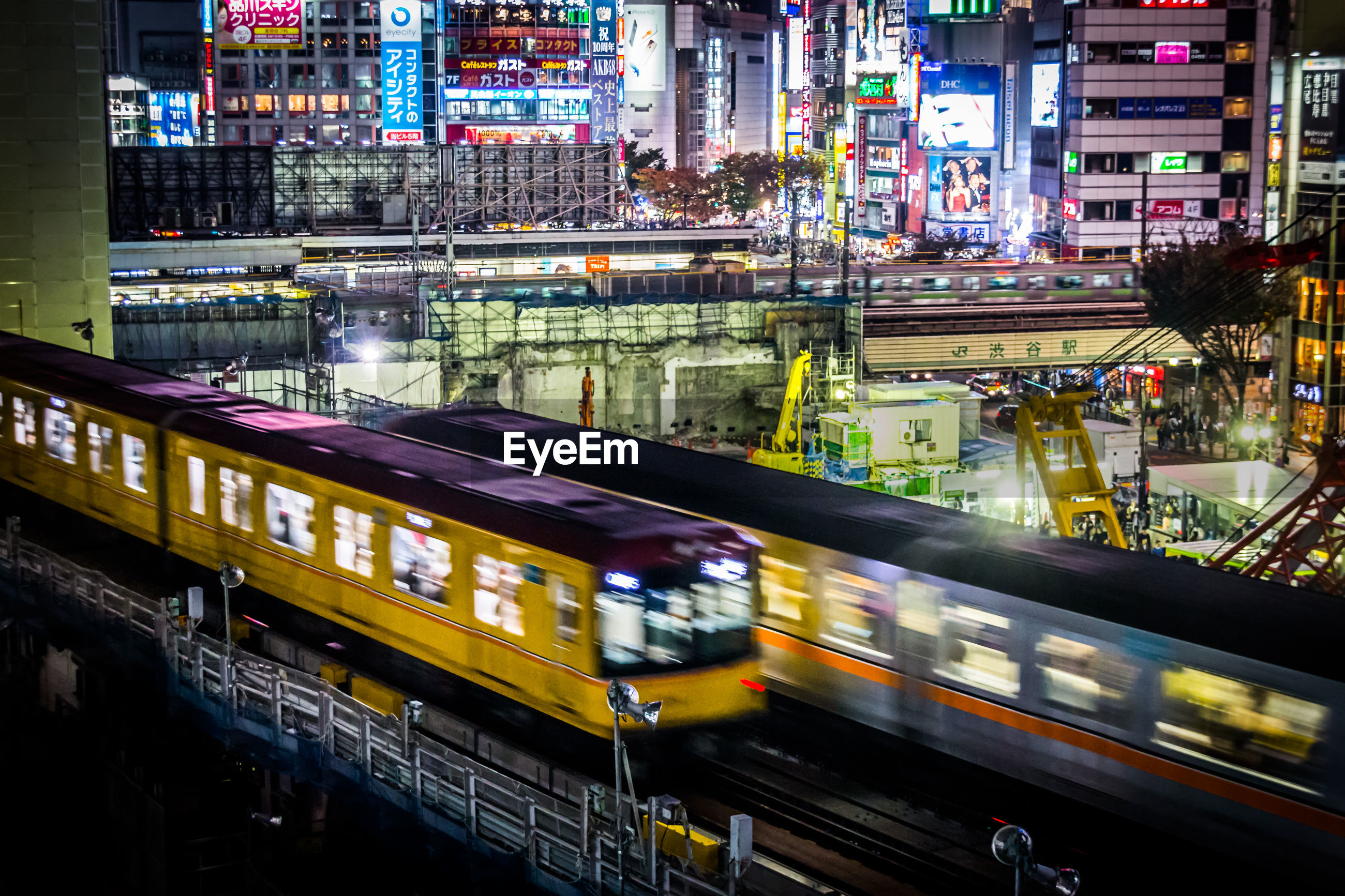 Blur image of illuminated trains against buildings at night