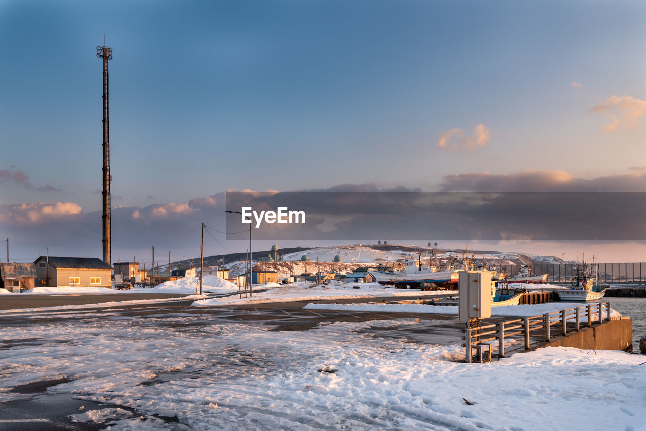 sky, winter, cold temperature, snow, architecture, cloud - sky, built structure, nature, industry, factory, building exterior, covering, no people, sunset, frozen, beauty in nature, smoke stack, outdoors, day