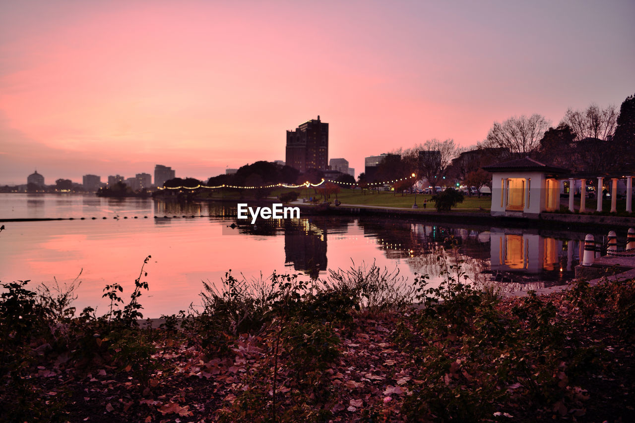 sunset, sky, water, building exterior, architecture, built structure, reflection, city, no people, nature, building, orange color, beauty in nature, lake, plant, scenics - nature, waterfront, outdoors
