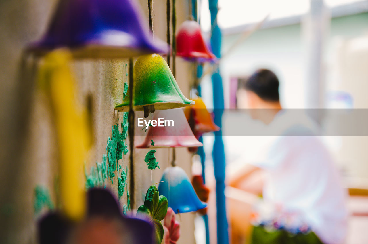 Close-up of colorful bells hanging by man