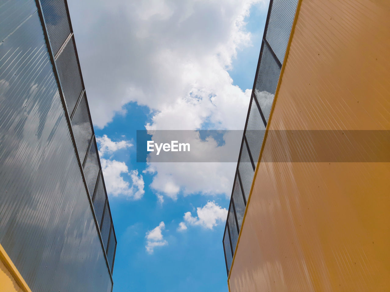 sky, cloud - sky, low angle view, architecture, built structure, building exterior, day, nature, no people, reflection, outdoors, building, sunlight, blue, glass - material, office building exterior, city, wall - building feature, metal, glass