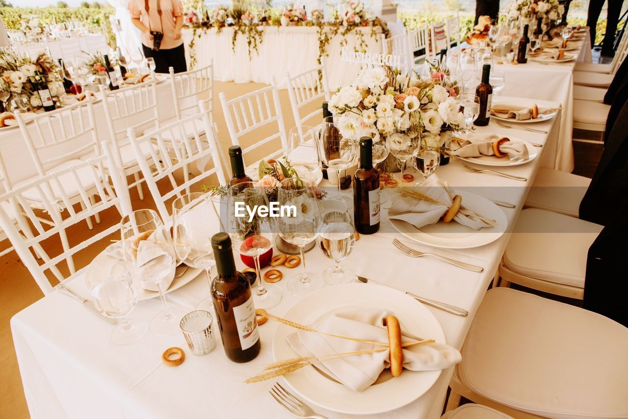 table, chair, household equipment, food and drink, kitchen utensil, setting, seat, place setting, eating utensil, tablecloth, restaurant, glass, arrangement, furniture, drinking glass, plate, flower, flowering plant, celebration, event, no people, luxury, crockery