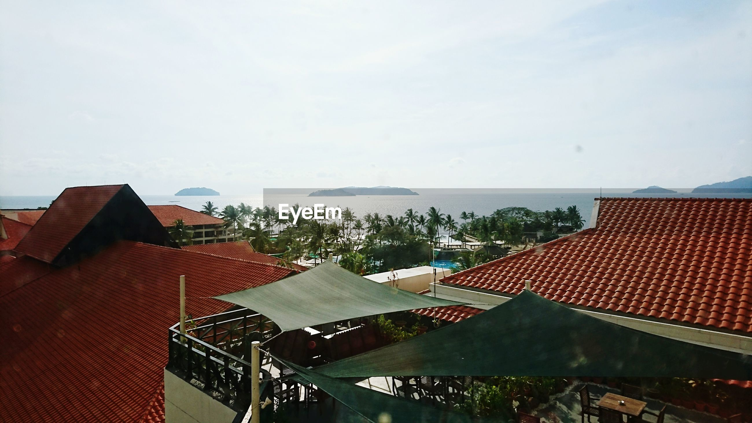 architecture, building exterior, built structure, roof, house, water, sky, high angle view, residential building, residential structure, sea, horizon over water, day, outdoors, roof tile, no people, clear sky, nature, town, residential district
