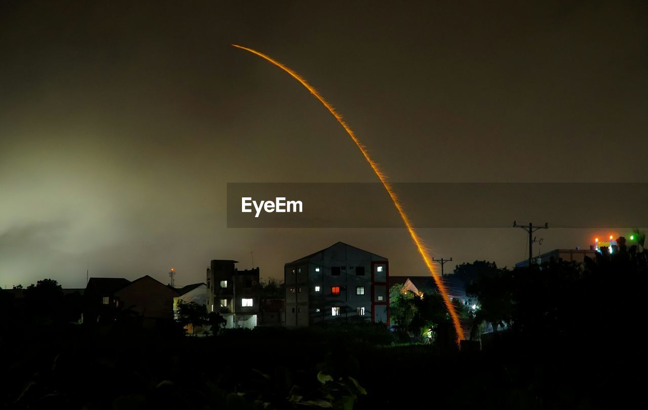 Lit rocket over houses against sky at night