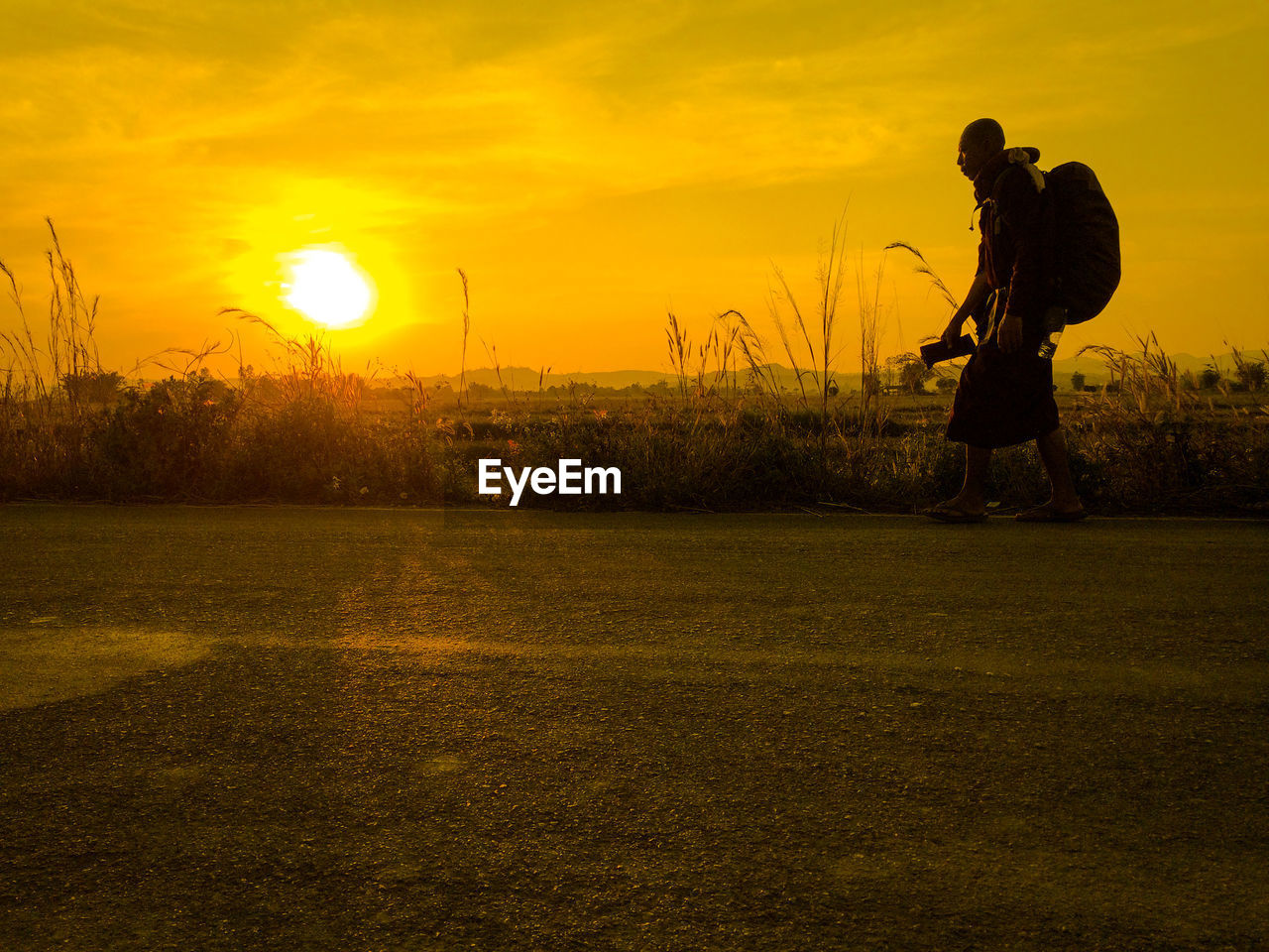 MAN PHOTOGRAPHING ON FIELD AT SUNSET