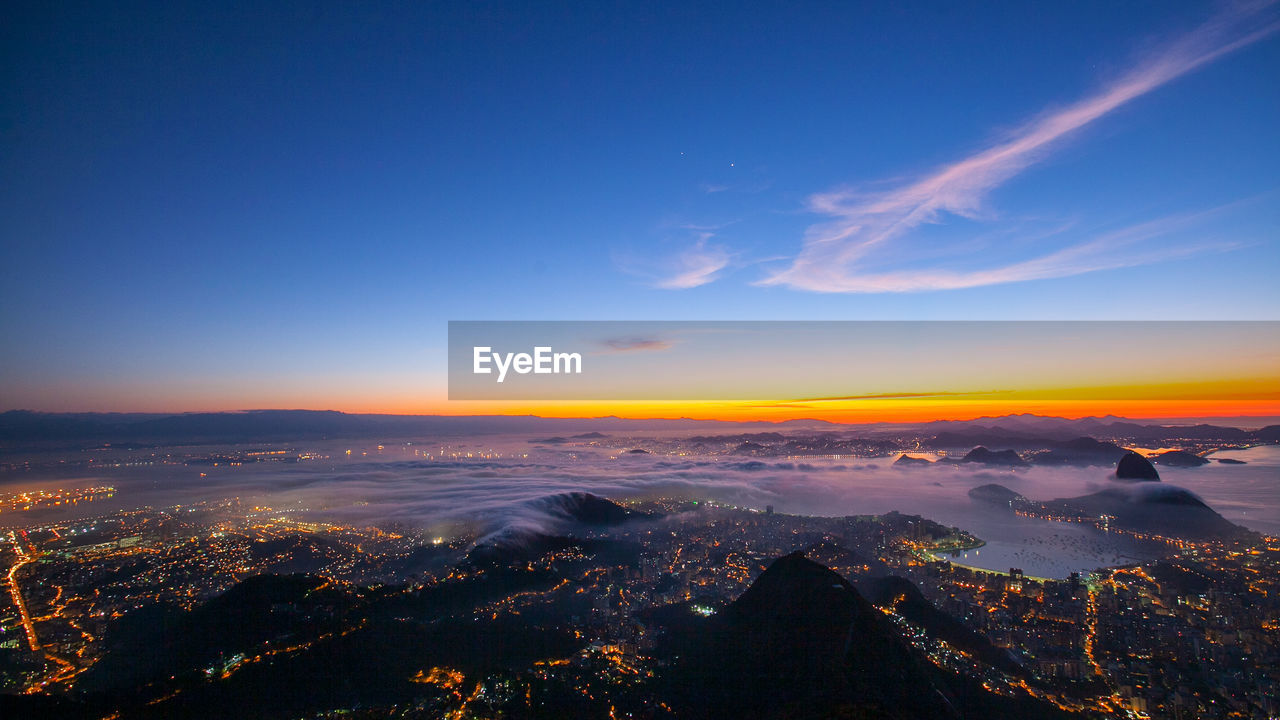 sky, scenics - nature, sunset, beauty in nature, cloud - sky, tranquil scene, orange color, nature, no people, tranquility, aerial view, mountain, blue, building exterior, environment, architecture, idyllic, outdoors, city, landscape, cityscape