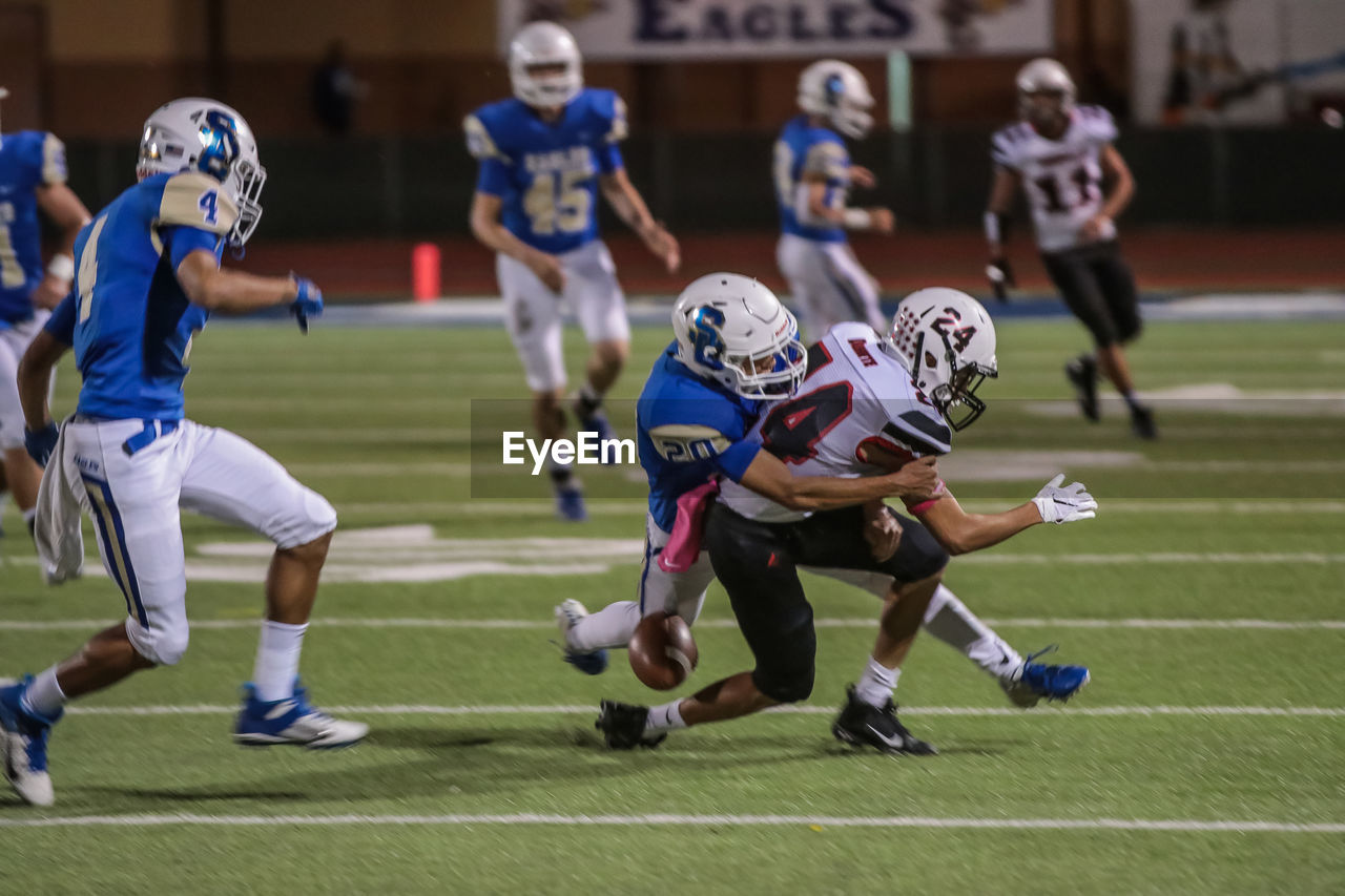 sport, competition, group of people, team sport, sports helmet, helmet, sports equipment, sports uniform, competitive sport, headwear, focus on foreground, clothing, athlete, american football - sport, stadium, playing, running, american football player, full length, people, teenager