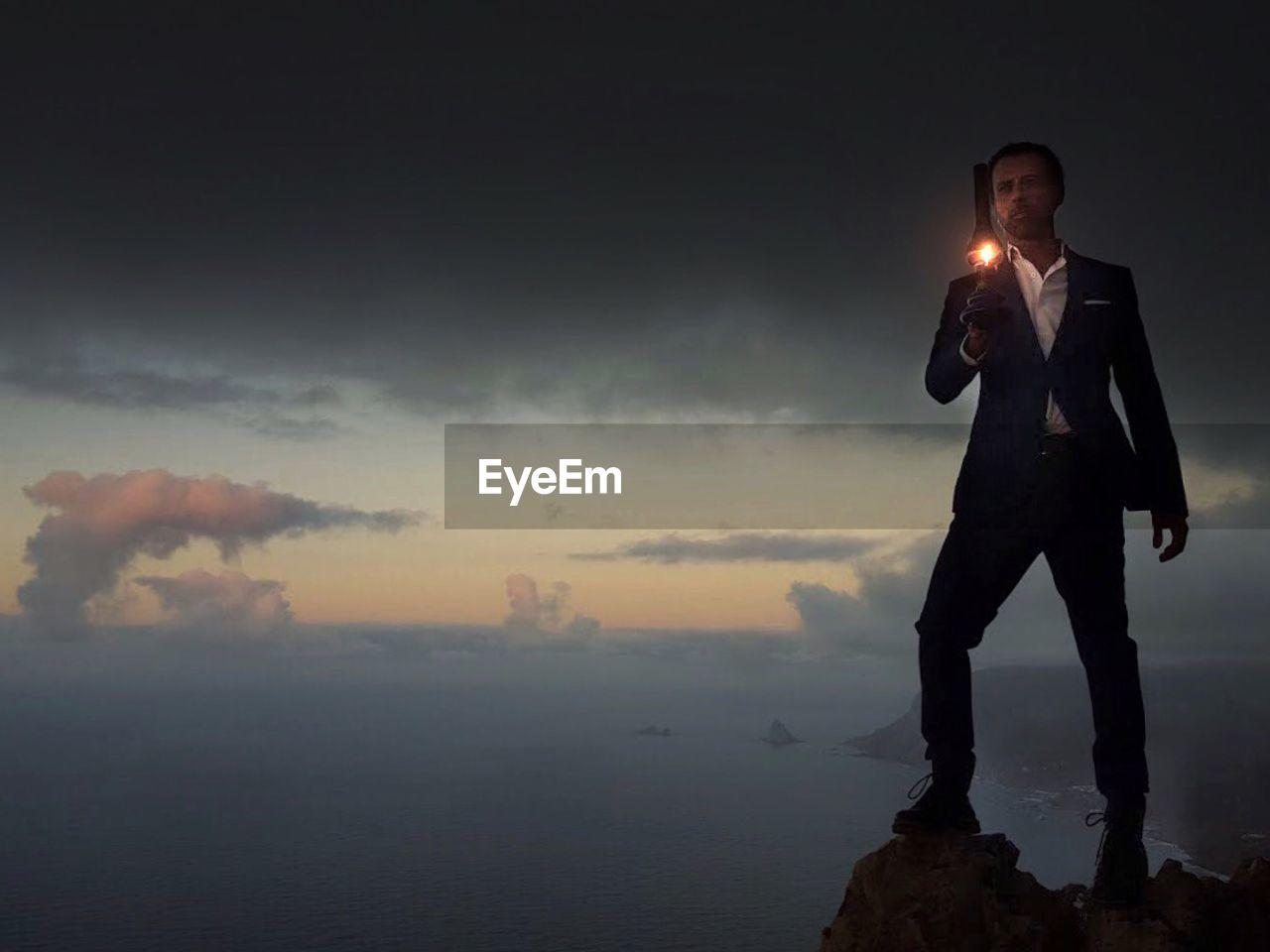 Full Length Of Man Holding Lantern While Standing On Cliff Against Sky