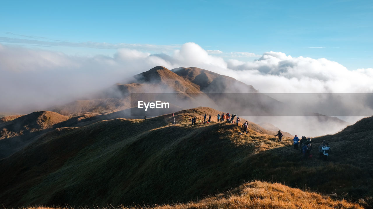 People hiking on mountain against cloudy sky