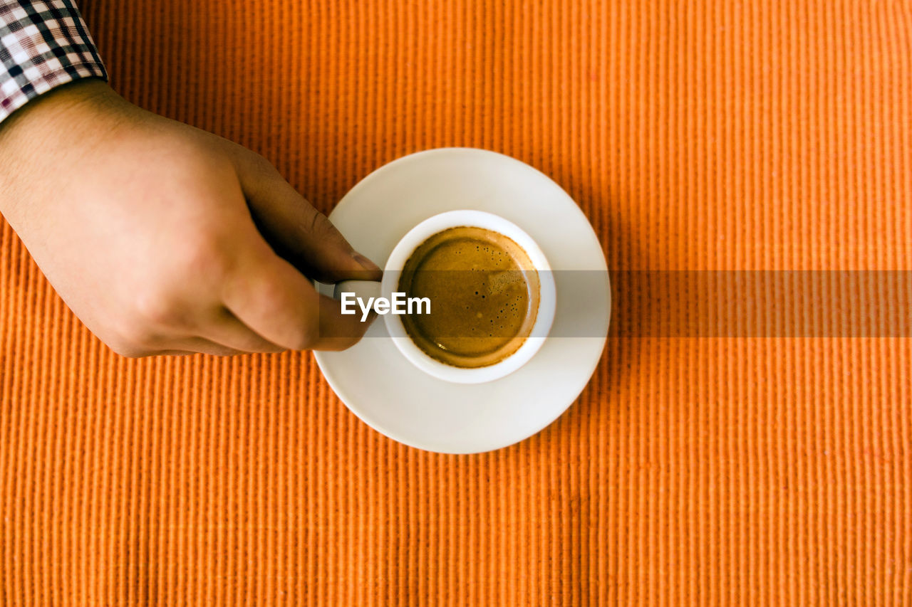 cup, one person, mug, food and drink, drink, coffee, holding, coffee cup, refreshment, coffee - drink, human hand, table, indoors, hand, freshness, human body part, real people, lifestyles, directly above, crockery, finger, non-alcoholic beverage