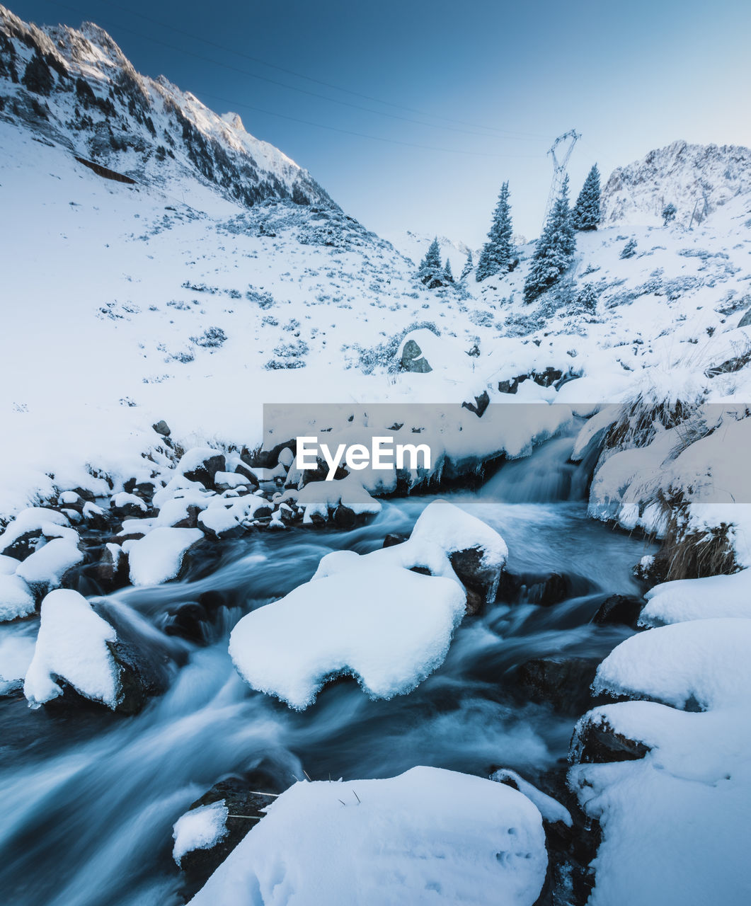 Scenic view of river flowing amidst snow covered mountains against clear sky