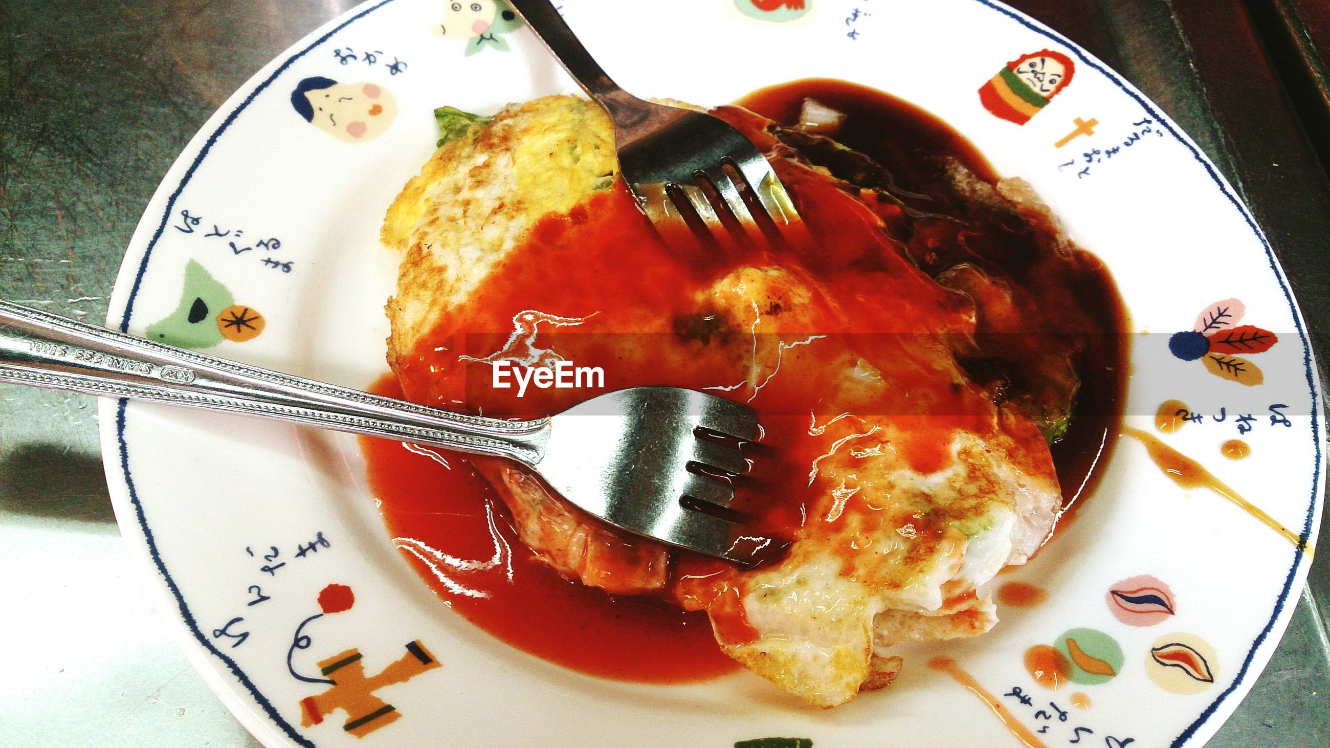 High angle view of oyster omelet with forks in plate