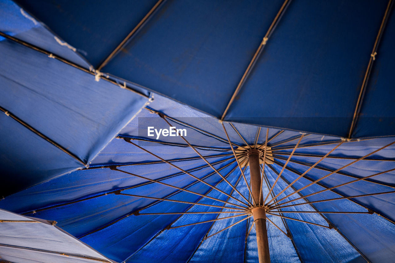 low angle view, umbrella, blue, pattern, no people, protection, architecture, day, security, parasol, built structure, shade, outdoors, metal, safety, sky, ceiling, sunlight, nature, directly below