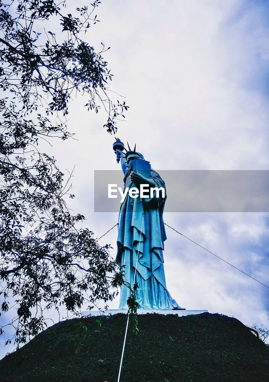 sky, cloud - sky, art and craft, low angle view, sculpture, statue, plant, tree, nature, human representation, representation, day, creativity, no people, male likeness, craft, blue, architecture, outdoors, female likeness