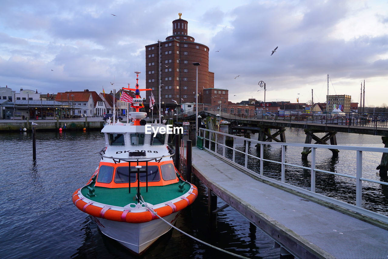 water, nautical vessel, transportation, cloud - sky, architecture, mode of transportation, building exterior, sky, built structure, river, nature, no people, moored, city, harbor, outdoors, waterfront, building, connection, passenger craft