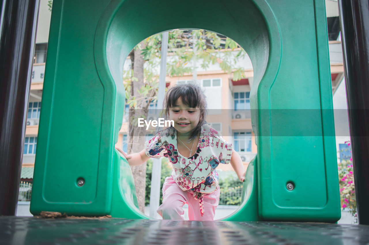 Cute smiling girl playing on slide in playground