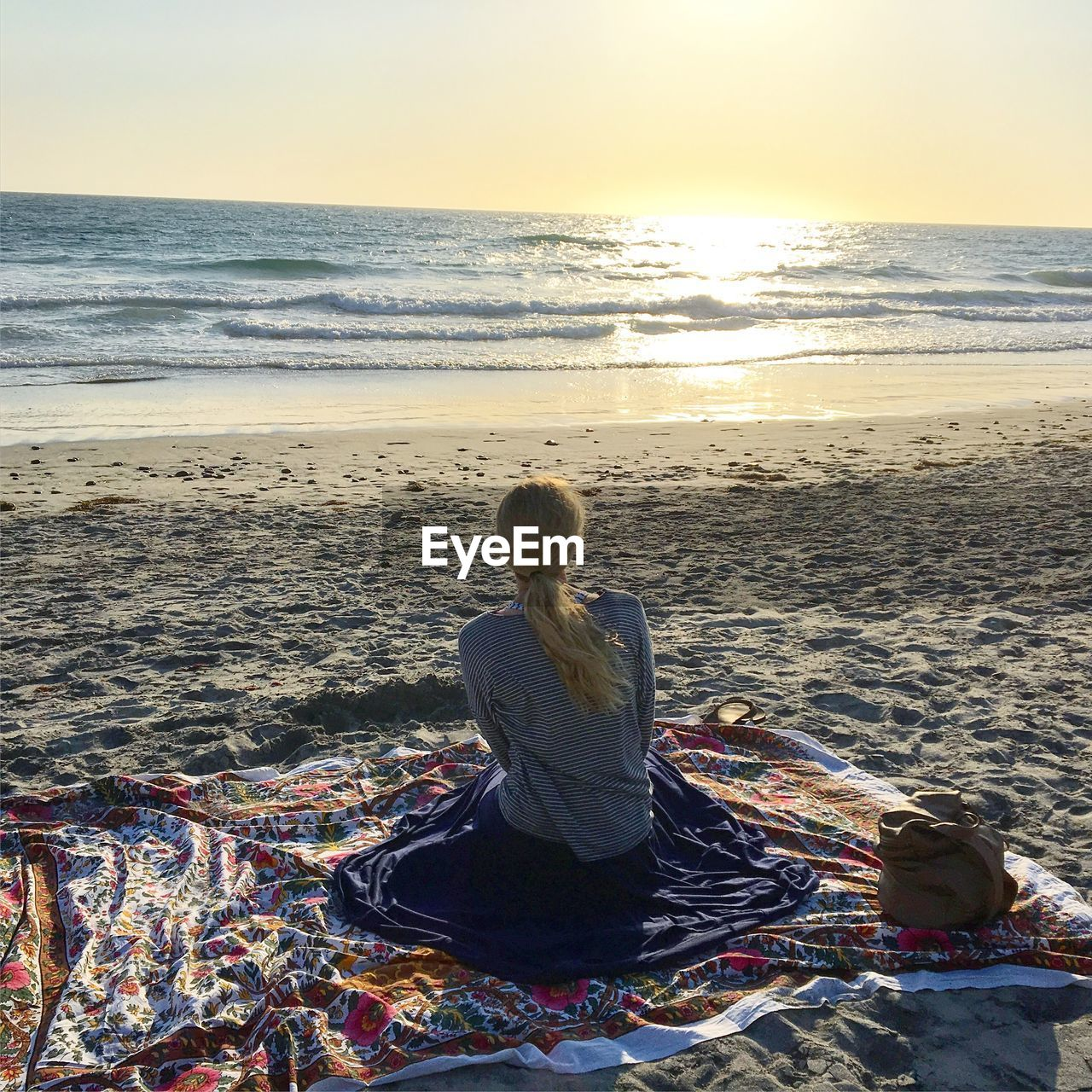 Rear View Of Woman Sitting On Beach Against Sky During Sunset