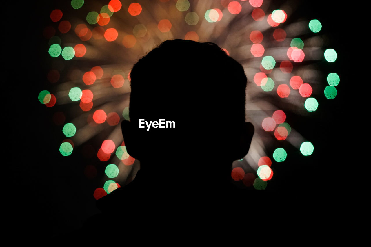 Close-up of man in front of illuminated fireworks