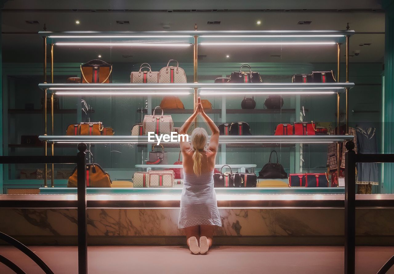 one person, real people, rear view, shelf, full length, indoors, lifestyles, standing, women, illuminated, blurred motion, adult, leisure activity, casual clothing, fashion, choice, clothing, human arm, arms raised