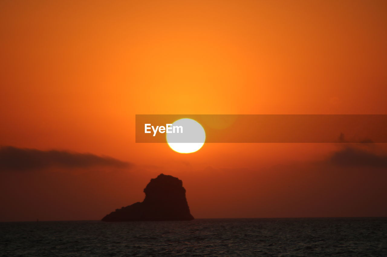 sunset, sky, beauty in nature, scenics - nature, sea, tranquil scene, tranquility, sun, orange color, water, idyllic, waterfront, nature, horizon over water, rock, silhouette, horizon, no people, outdoors, romantic sky, stack rock