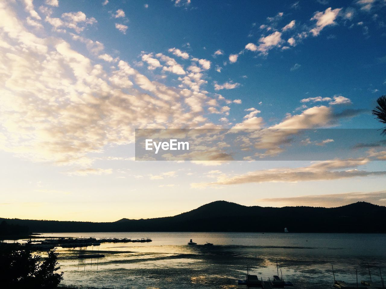Scenic view of river and silhouette mountain against sky during sunset