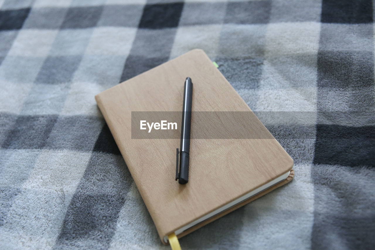 pen, still life, high angle view, table, no people, indoors, simplicity, paper, checked pattern, close-up, tablecloth, day, textile, two objects, connection, focus on foreground, technology, gray, communication, note pad