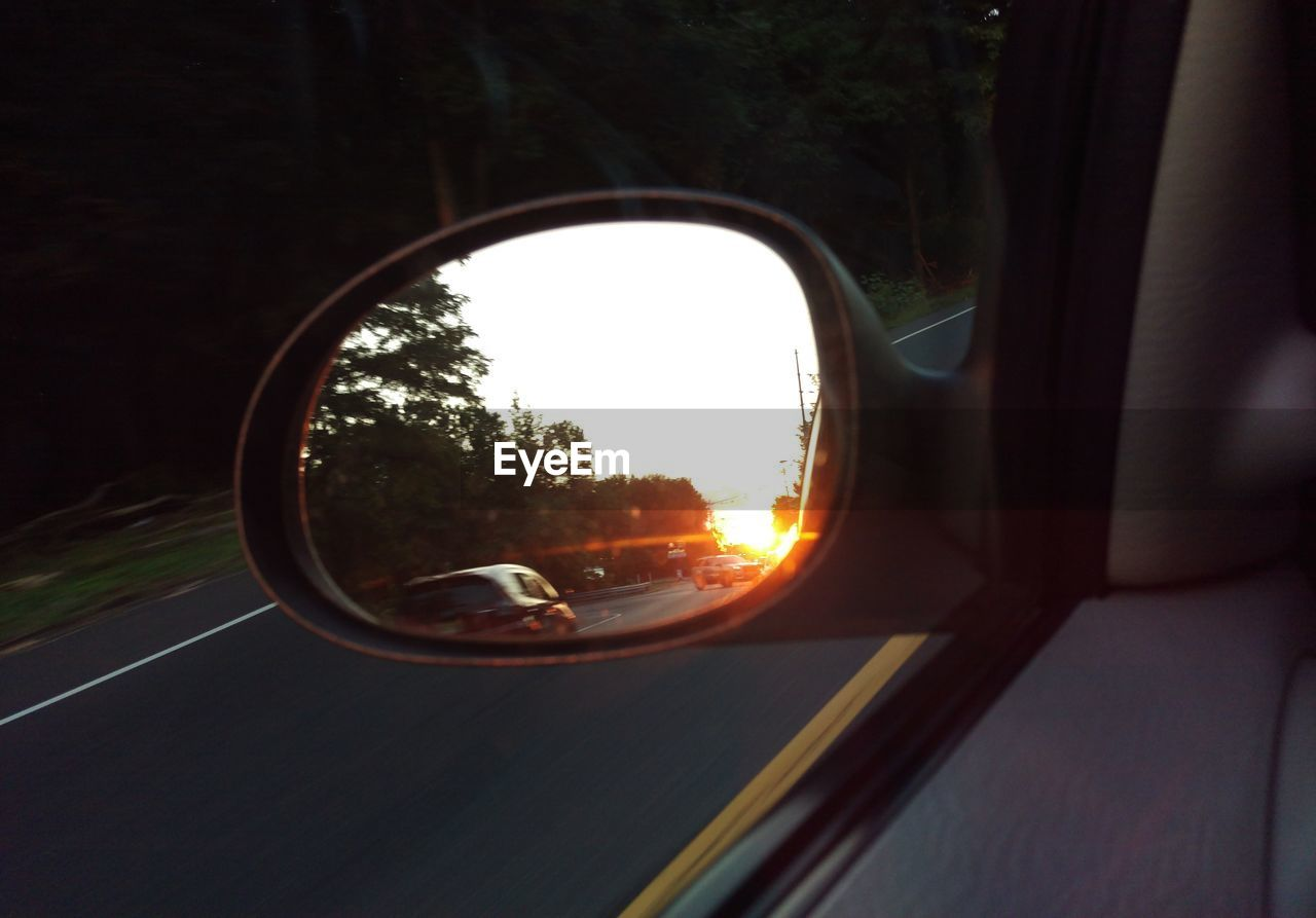 side-view mirror, transportation, car, mode of transport, reflection, land vehicle, sunset, mirror, vehicle mirror, window, tree, journey, sun, road trip, nature, road, outdoors, close-up, real people, day, sky