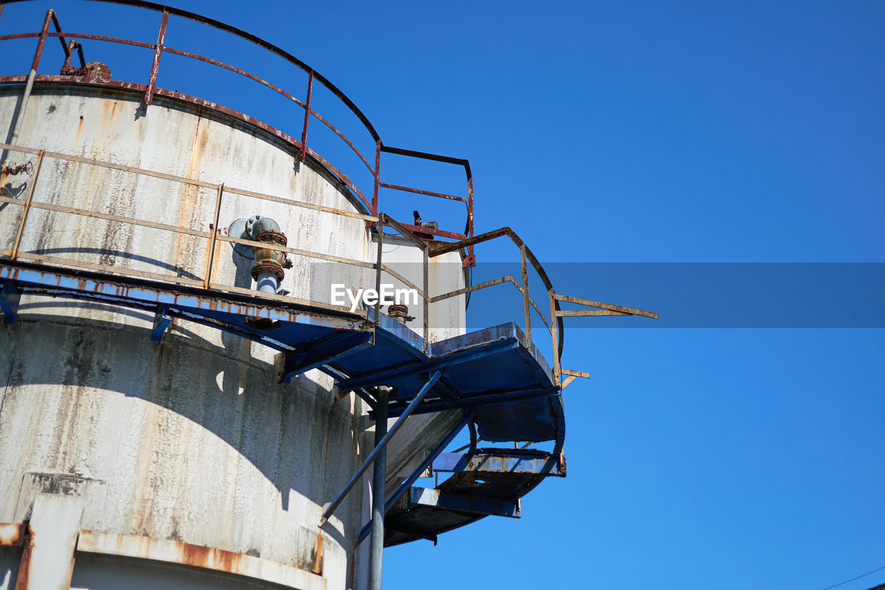 low angle view, sky, industry, clear sky, nature, day, storage tank, blue, fuel and power generation, built structure, architecture, outdoors, refinery, copy space, factory, sunlight, oil refinery, oil industry, storage compartment, metal, industrial equipment