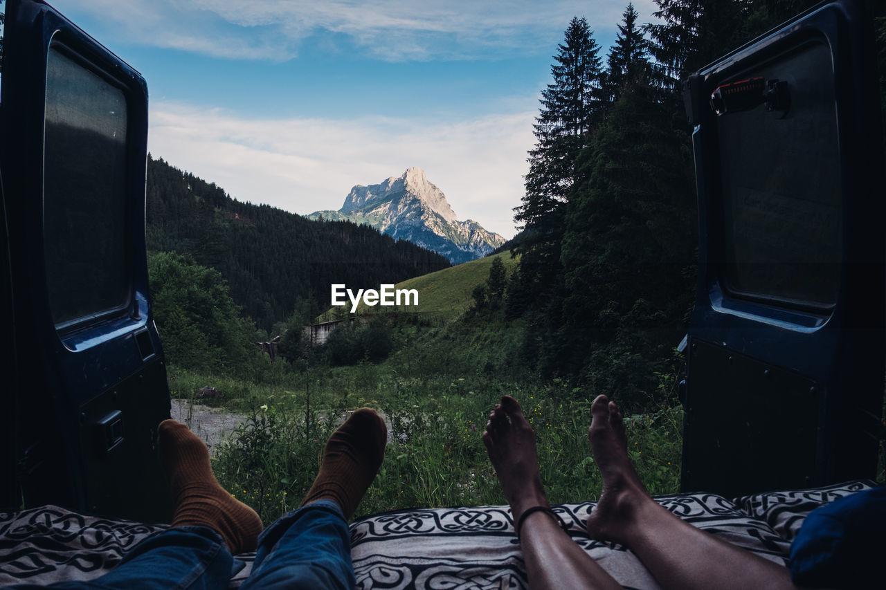 Low Section Of People Relaxing In Camper Van