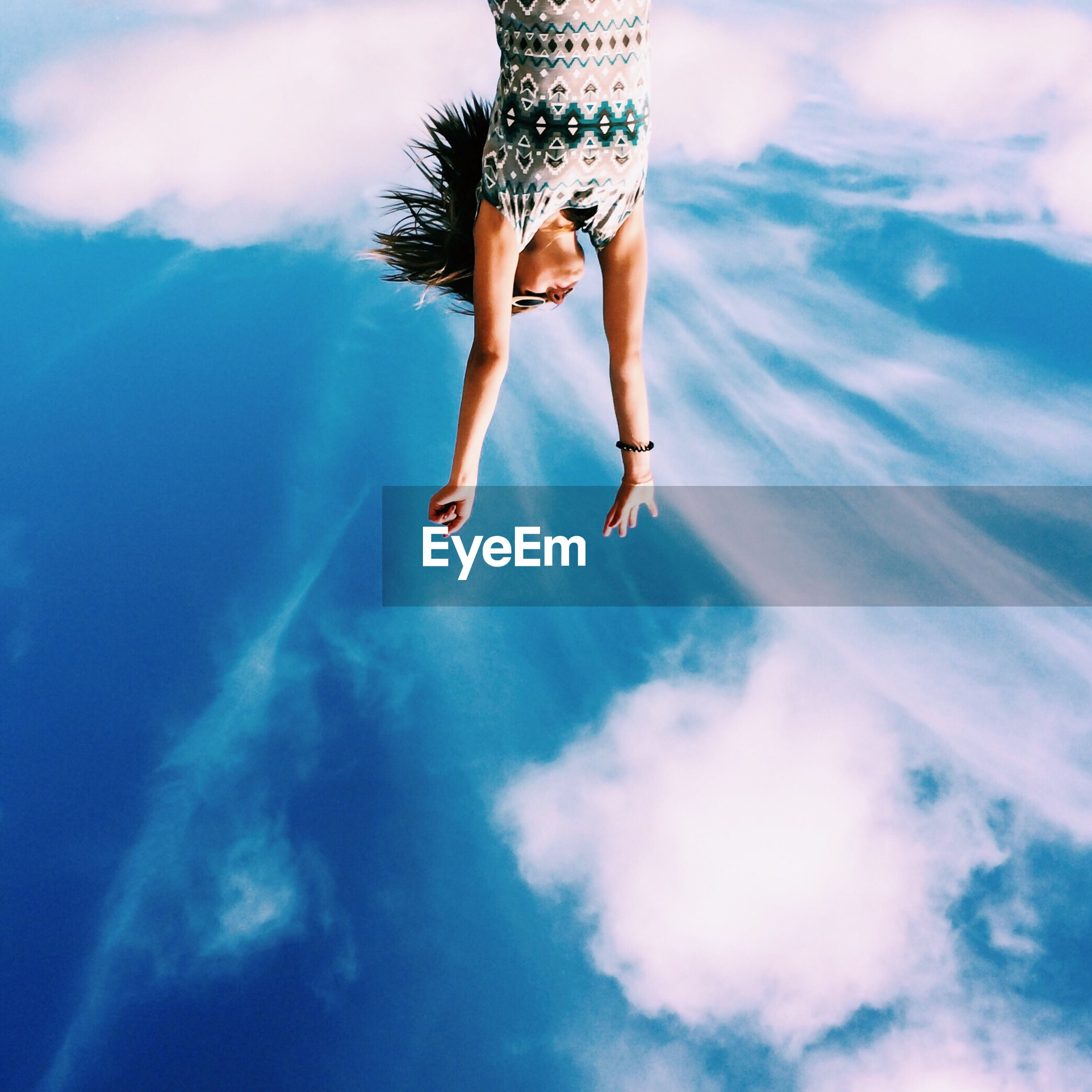Upside down image of young woman with arms raised against sky