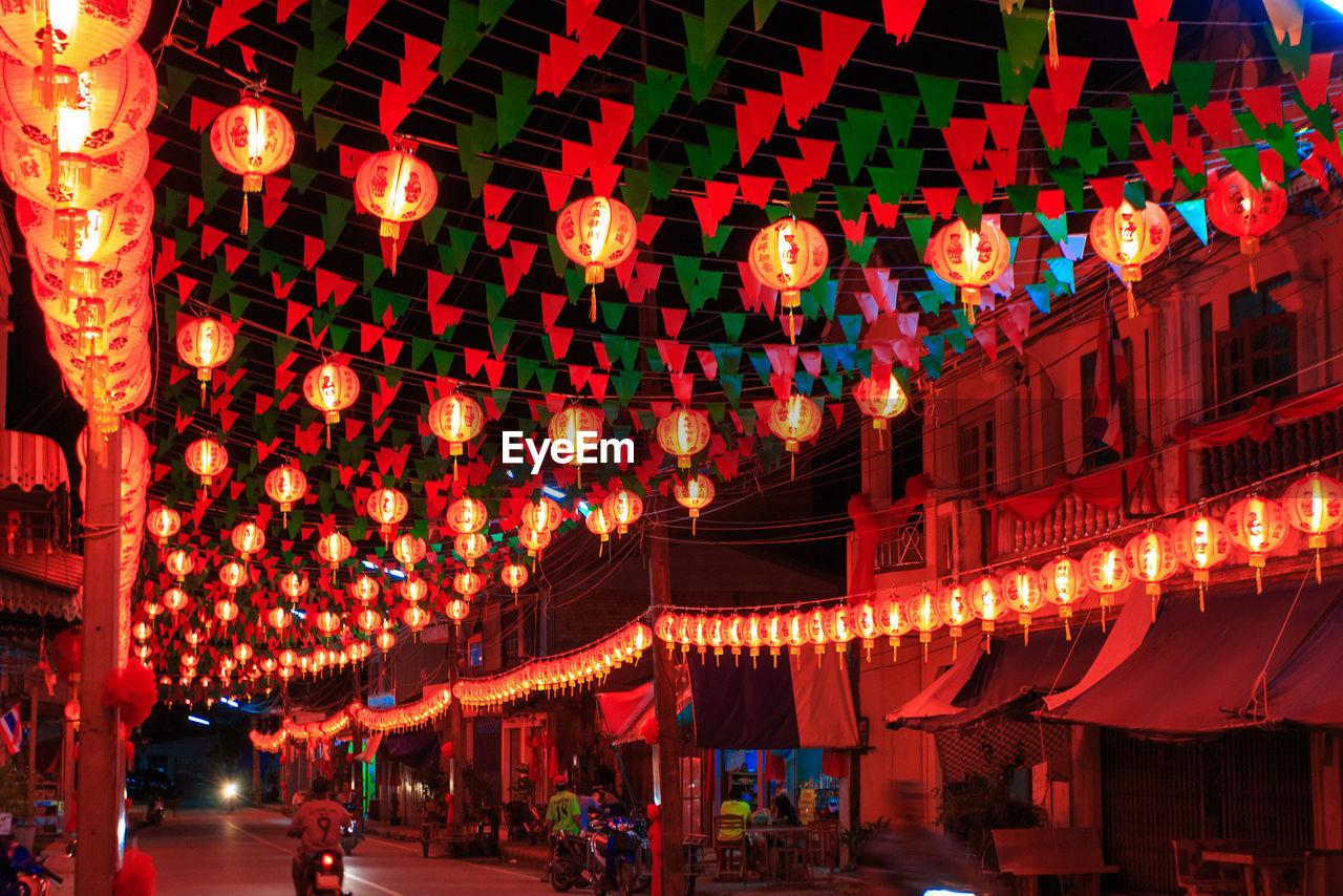 Illuminated Lanterns Hanging Over Street At Night