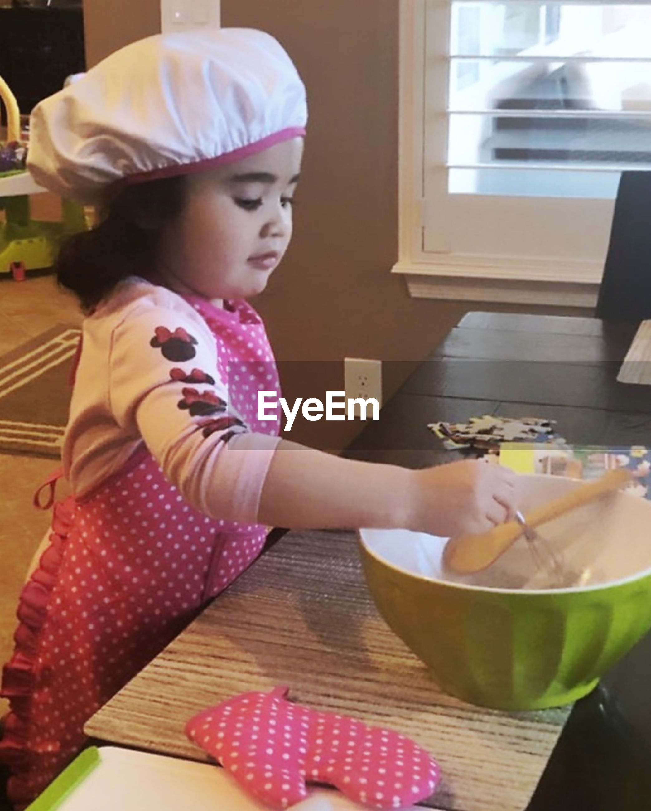 Cute girl preparing food on table at home