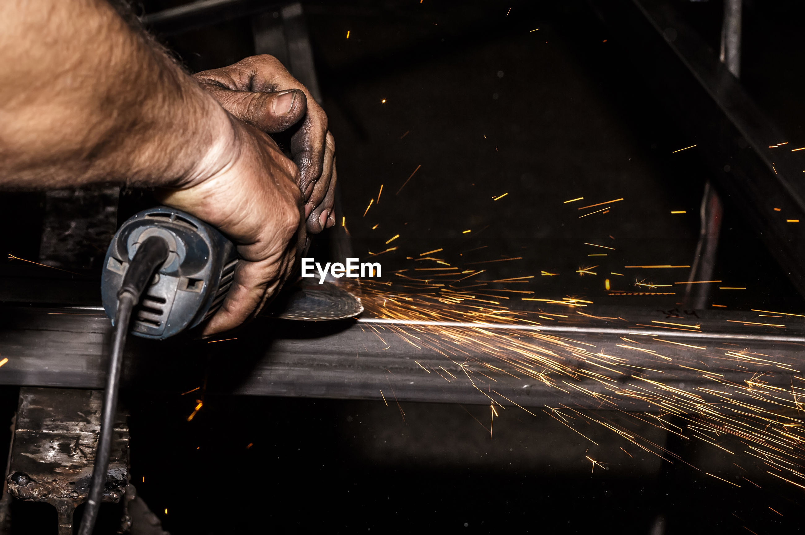 Close-up of manual worker using machinery while working at night