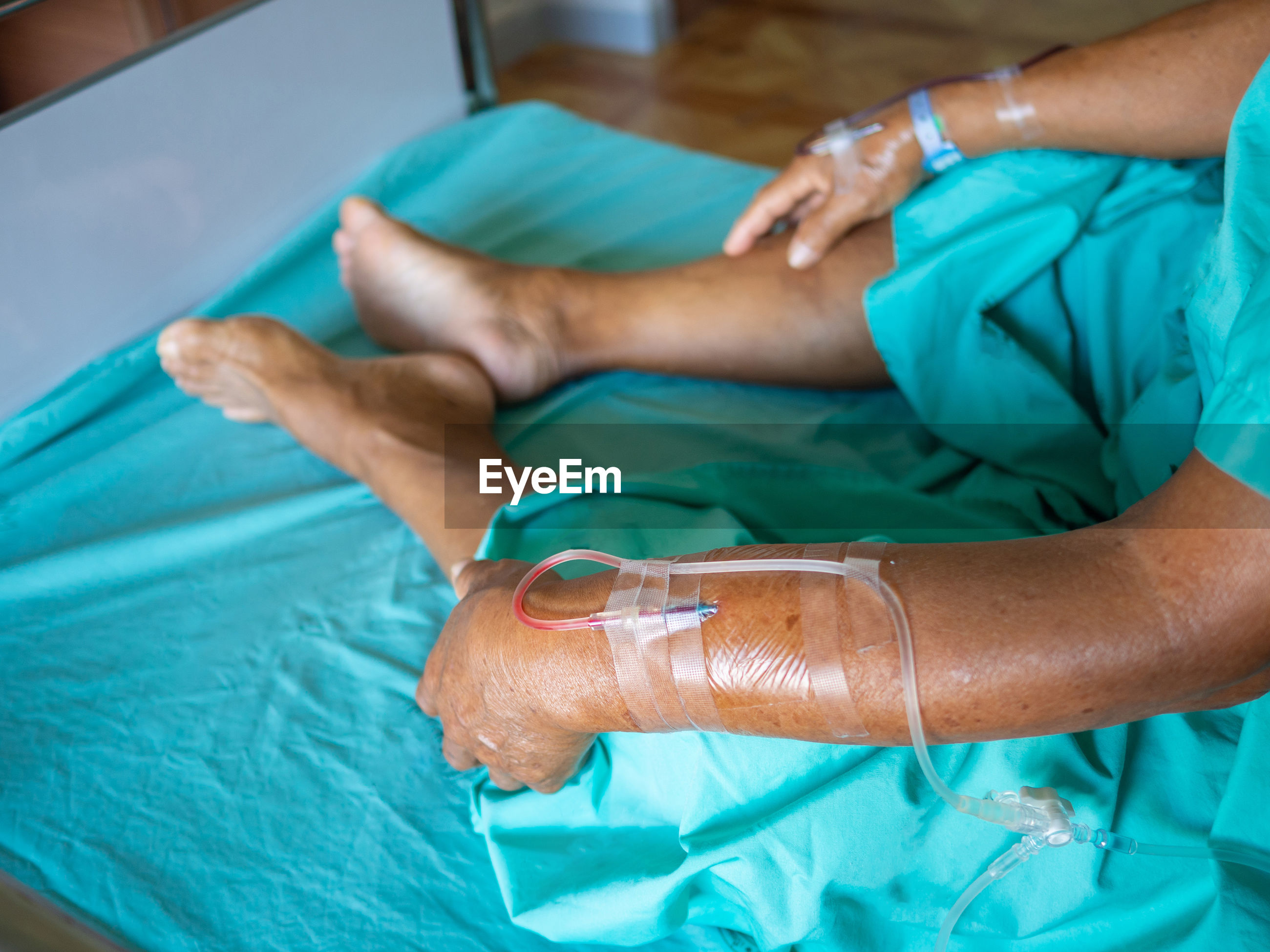 Low section of patient sitting on bed in hospital ward