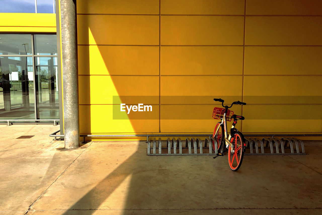 bicycle, transportation, architecture, land vehicle, mode of transportation, wall - building feature, sunlight, shadow, built structure, city, flooring, building exterior, day, stationary, outdoors, nature, no people, tile, orange color, footpath, architectural column, tiled floor