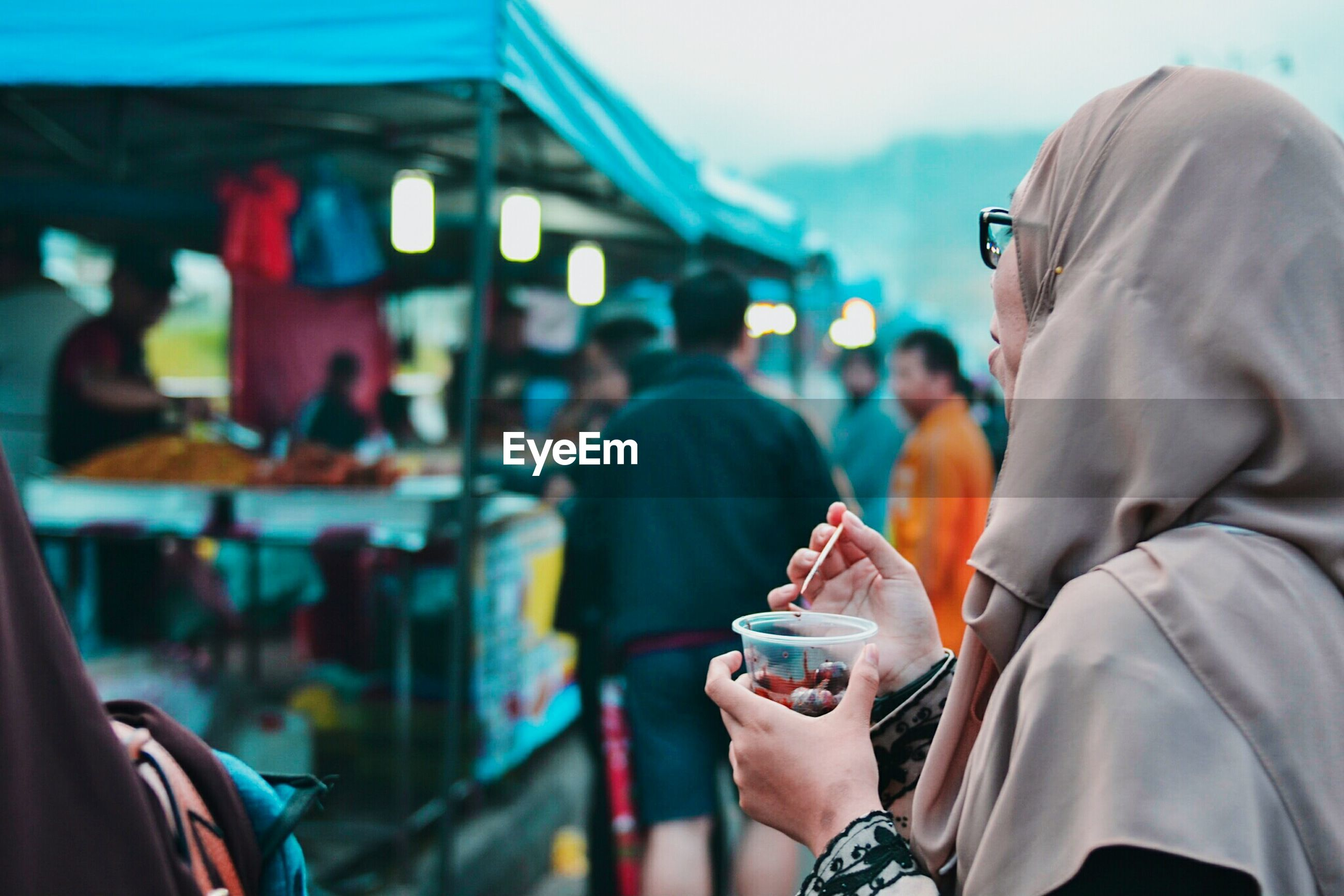 Woman having food at market stall