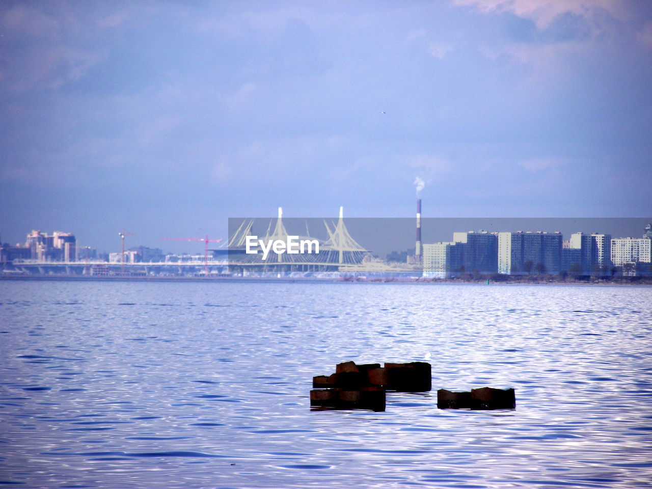 water, architecture, waterfront, sky, built structure, building exterior, industry, city, cloud - sky, crane - construction machinery, transportation, nature, no people, sea, day, machinery, outdoors, business, skyscraper, office building exterior, bay