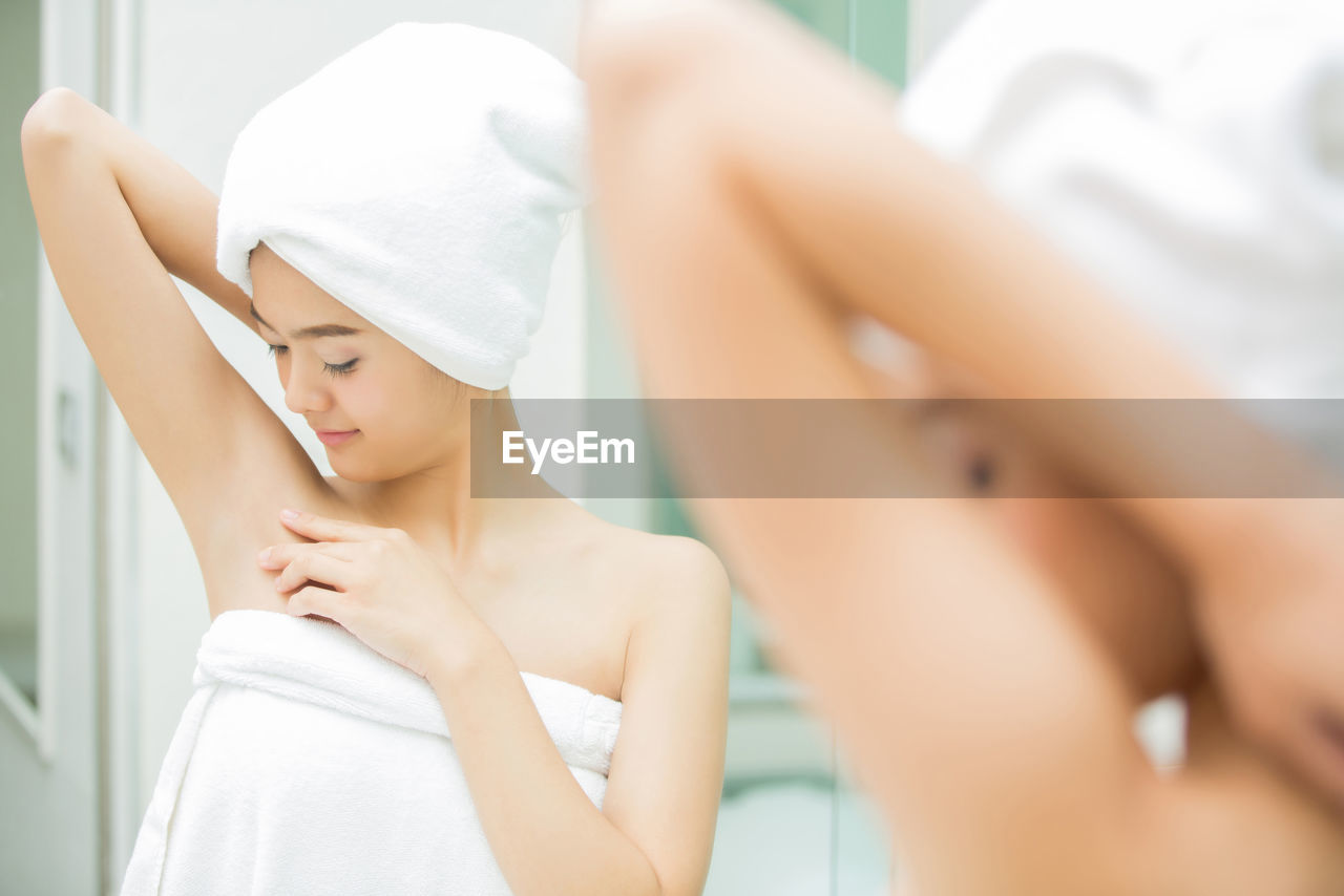 Rear View Of Young Woman Wrapped In Towel Reflecting On Mirror At Home