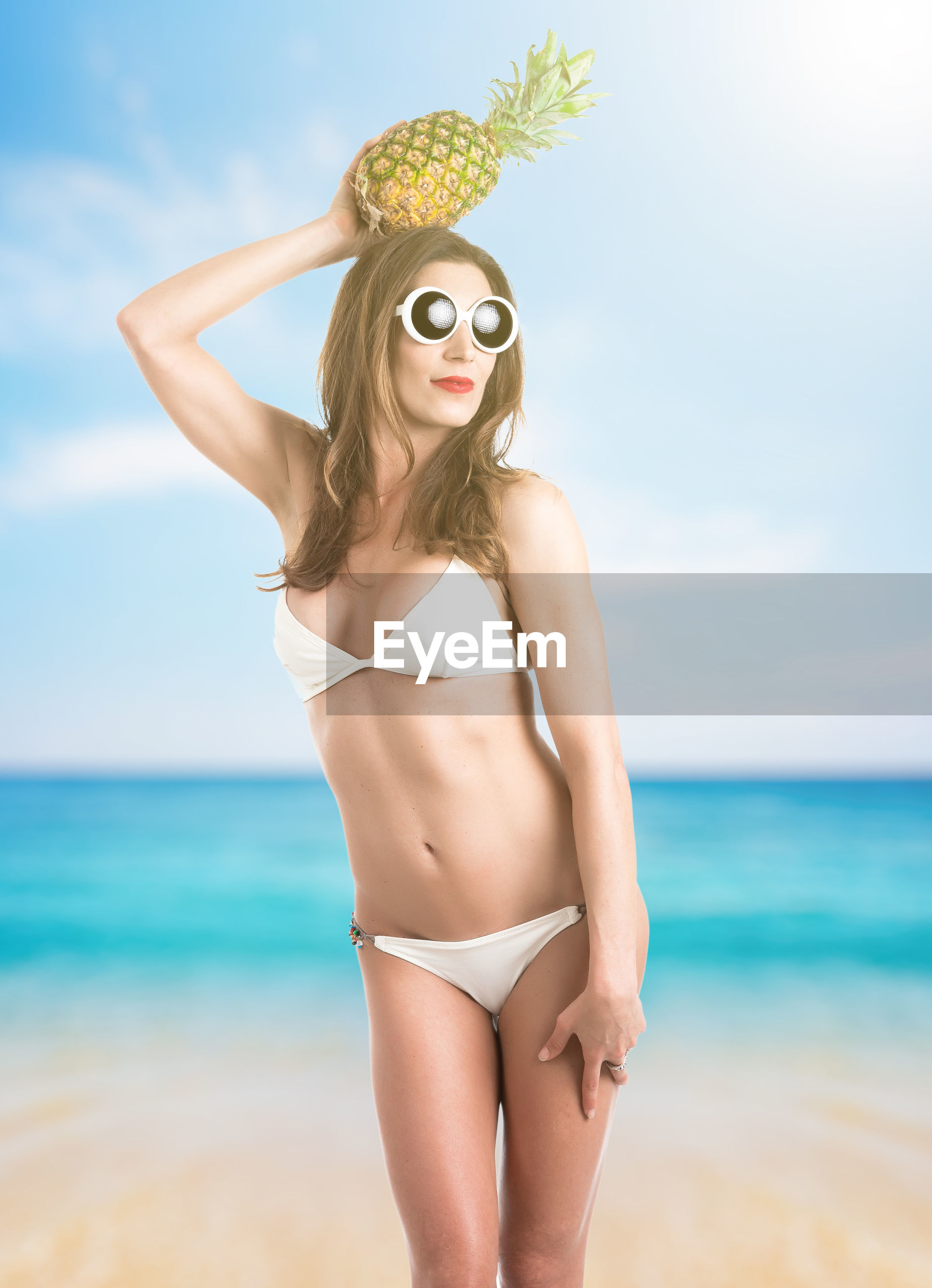 Woman holding pineapple while standing at beach