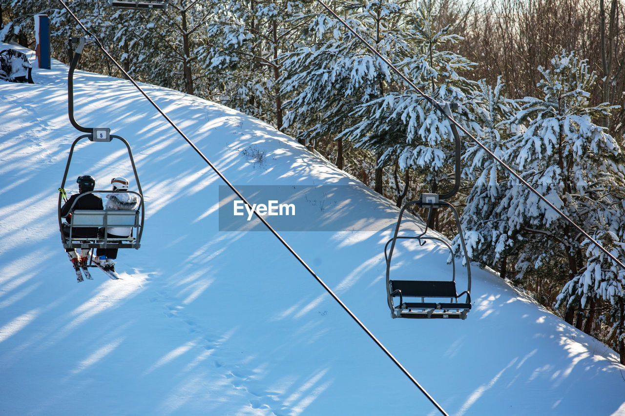 tree, plant, nature, winter, snow, day, mode of transportation, transportation, cold temperature, real people, sky, cable car, leisure activity, outdoors, lifestyles, ski lift, beauty in nature, sunlight, two people, snowcapped mountain