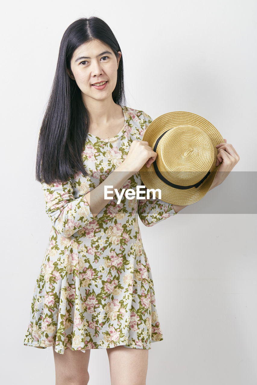 one person, three quarter length, standing, front view, hat, looking at camera, clothing, women, holding, leisure activity, portrait, indoors, lifestyles, casual clothing, studio shot, real people, young women, white background, adult, fashion, hair, hairstyle, beautiful woman, floral pattern