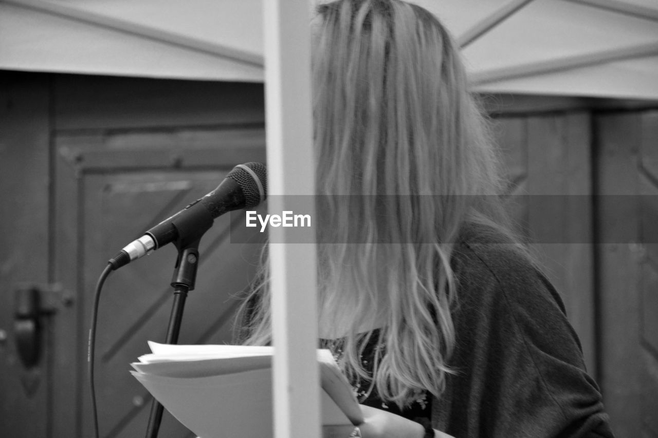 real people, one person, microphone, focus on foreground, indoors, music, day, blond hair, close-up, young adult, people